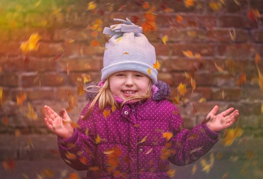Portrait of a cute girl with swirling leaves in autumn