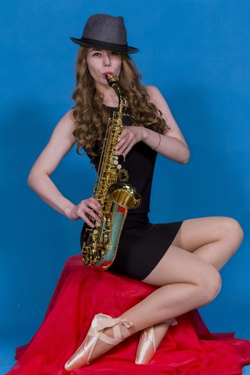 girl in Pointe and saxophone on a red silk on a blue background in the Studio
