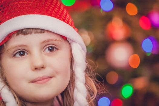 Cute Christmas girl with the Christmas tree lights bokeh in the background