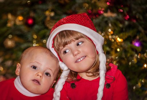 Portrait of  siblings - brother and sister, sitting in front of the Christmas tree