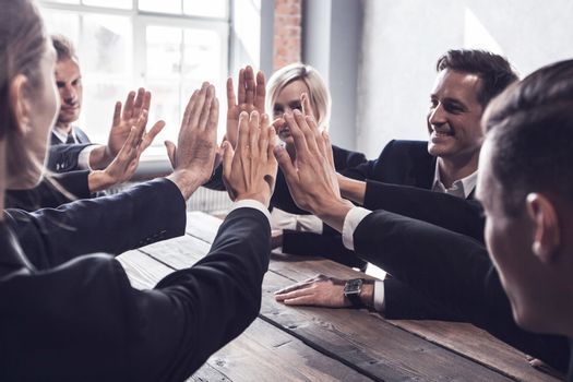 Business people give high five at business meeting