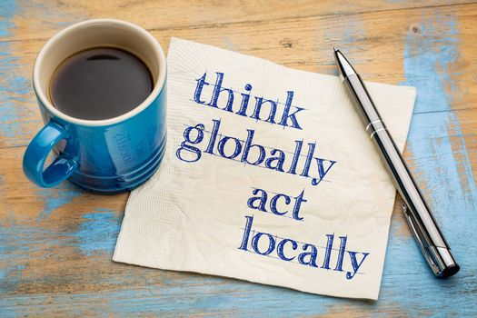 Think globally, act locally reminder - handwriting on a napkin with a cup of espresso coffee