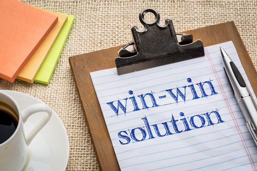 win-win solution concept - handwriting on a clipboard with a cup of coffee