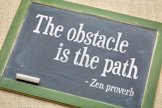 The obstacle is the path Zen proverb on a vintage slate blackboard with a white chalk against burlap canvas