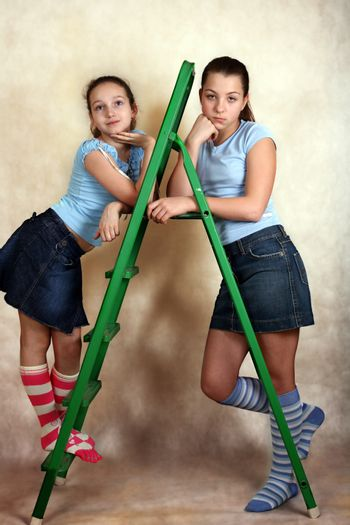 Portrait of the young girls with step-ladder on a yellow background