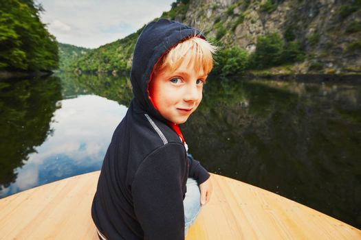 Little traveler on the river. Boy is sitting on the boat.