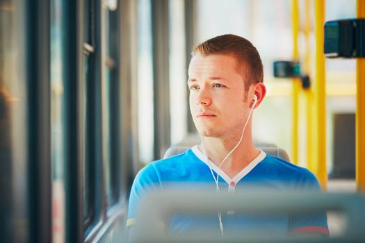 Everyday life and commuting to work by public transportation. Handsome young man is traveling by tram (streetcar). Man is wearing headphones and listening to music. Prague, Czech Republic