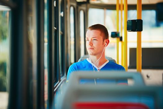 Loneliness man is wearing headphones and listening to music. Everyday life and commuting to work by public transportation. Handsome young man is traveling by tram.