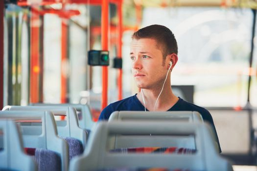 Sad young man is traveling by tram (bus). Everyday life and commuting to work by public transportation. Man is wearing headphones and listening to music.