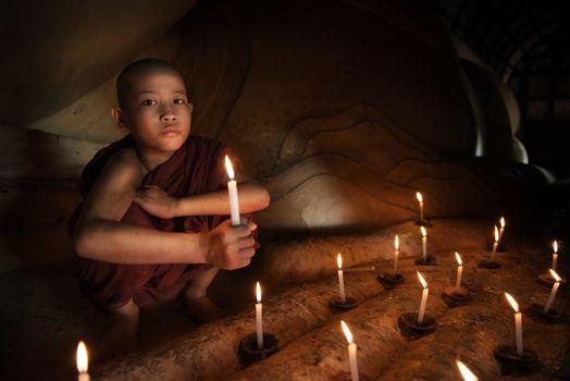 Buddhist novice with candlelight