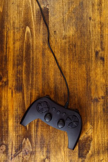 Game pad controller on wooden desk, flat lay top view