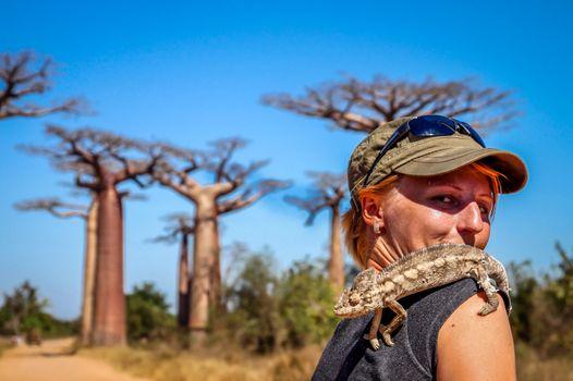 Girl and chameleon in the Avenida de Baobab in Madagascar