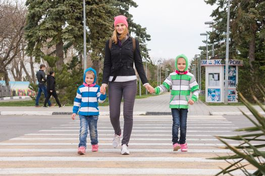 Anapa, Russia - March 9, 2016: a young mother with two daughters cross the road at a pedestrian crossing
