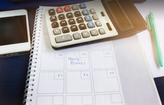 Organiser book with text yearly bonus and background of calcula
