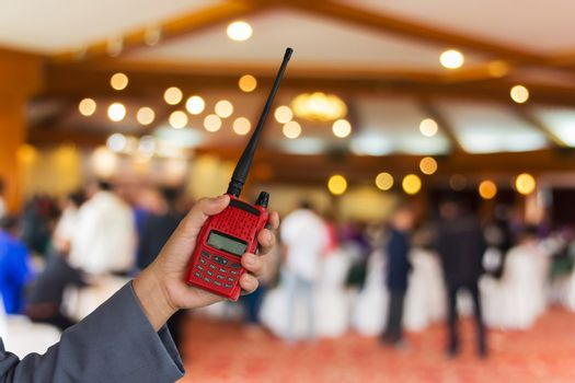 Red radio communication in hand with blurred people in convention hall background and copy space