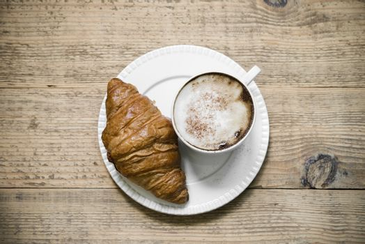 Cup of latte macchiato and croissant on wooden table