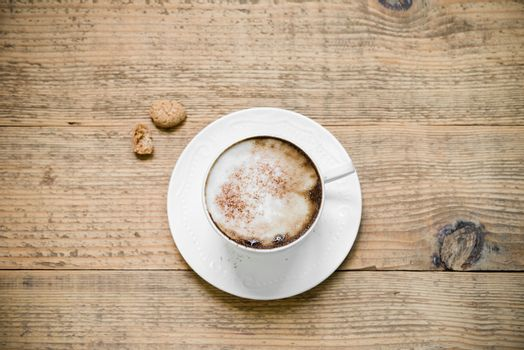 Cup of cappuccino with biscotti on woode table