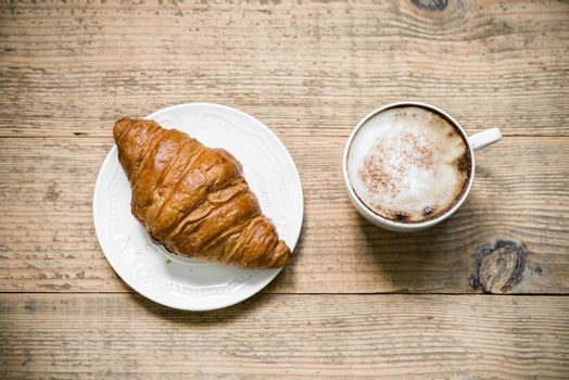 Cup of cafe latte and croissant on wooden table