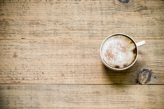 Cup of cafe latte or cappuccino on wooden table. Top view