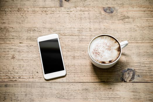 Cup of cafe latte with white smartphone on wooden table