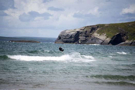 lone kite surfer surfing the waves at ballybunion beach on the wild atlantic way