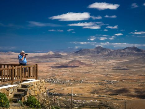 Man taking pictures of a Fuerteventura landscape from the viewing platform of the Morro Velosa viewpoint, Fuerteventura,  Canary Islands, Spain. Picture taken 13 April 2016