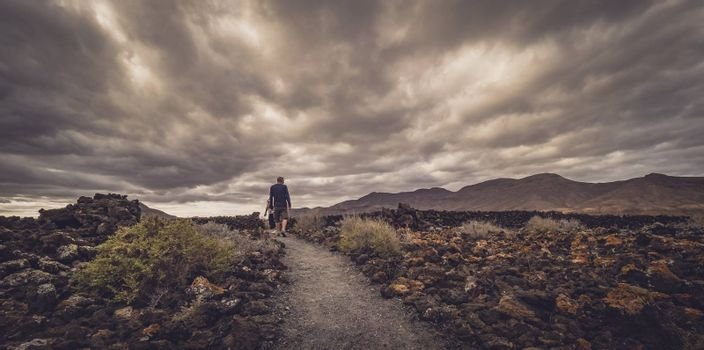 Man walking on a path leading towards the archaeological site of an old aboriginal village in Fuerteventura, Canary Islands, Spain. Picture taken 13 April 2016