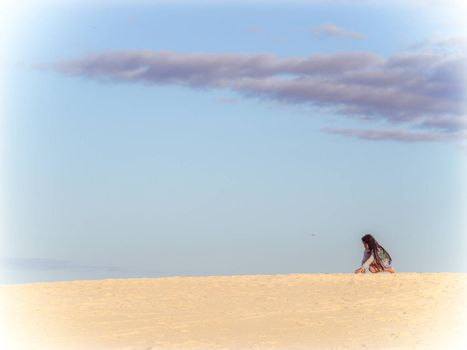 Girl sitting on top of the stunning sand dunes in the Natural Reserve of Dunes of Corralejo in Fuerteventura, Canary Islands, Spain. Picture taken 13 April 2016