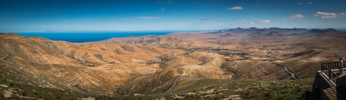 Man standing on a viewing platform and admiring the panoramic view of the landscape of Fuerteventura, Morro Velosa viewpoint, Canary Islands, Spain. Picture taken 13 April 2016.