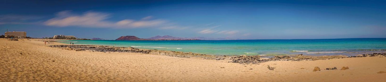 Panoramic view of wide sandy beach of Corralejo in Corralejo Dunes National Park in Fuerteventura, Canary Island, Spain with Los Lobos Island in the background. Picture taken 15 April 2016.