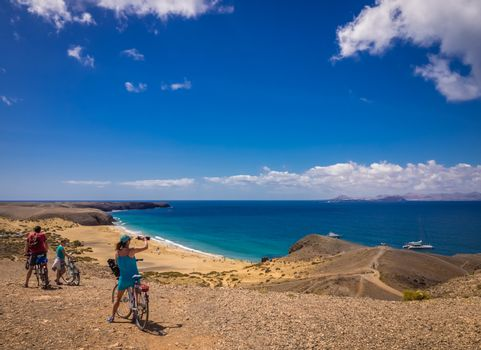 People on bicycles admiring the view of Playa Mujeres in Lanzarote, Canary Islands, Spain. Picture taken 20 April 2016.