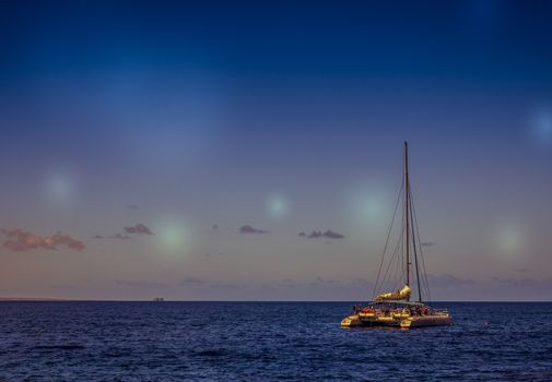 Private catamaran on the ocean at dusk, Canary Islands, Spain. Picture taken 20 April 2016.