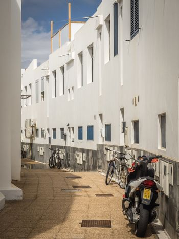Motorbike and bicycles parked in a narrow street in Playa Blanca, Lanzarote, Canary Islands, Spain. Picture taken 19 April 2016
