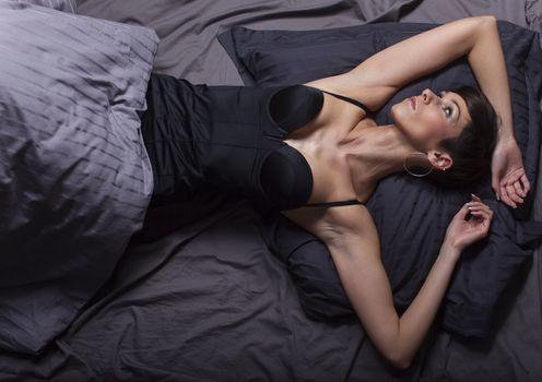brunette woman lying in bed