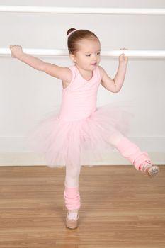 Little ballerina wearing a tutu dancing at the barre