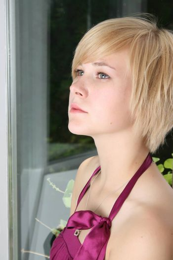 Beautiful blond female leaning against a door, expressing sadness and loneliness