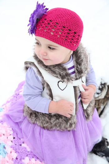 Little girl sitting outside in the snow