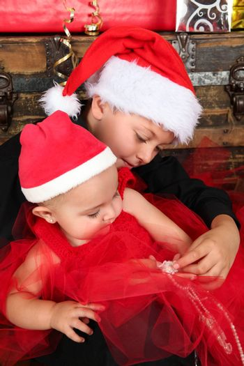 Christmas baby and her brother wearing a red hats