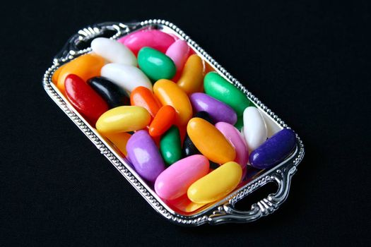 Multi colored candies on a tray with black background
