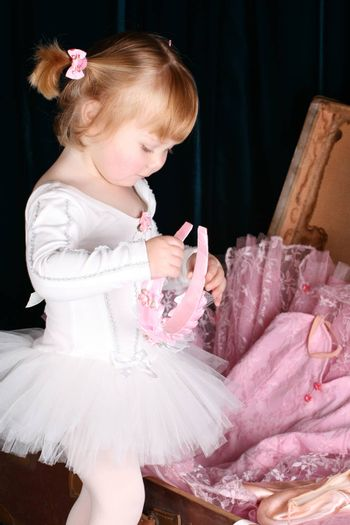 Sweet little ballet girl unpacking a suitcase with costumes