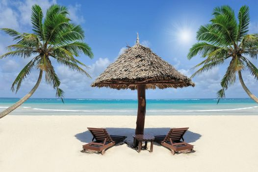 Beautiful tropical beach witn straw umbrella and palm. Straw umbrella and palm at the beach