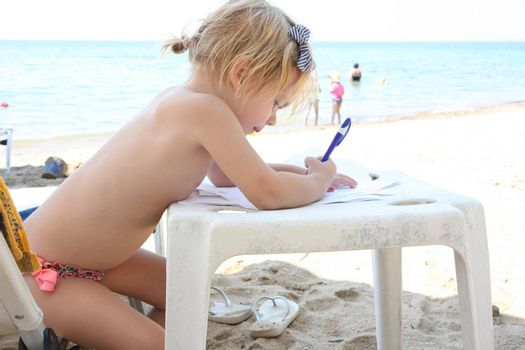 Cute baby girl drawing on the beach