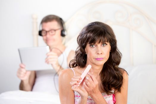 Upset Woman Gestures Regarding  Man in Bed with Computer Tablet