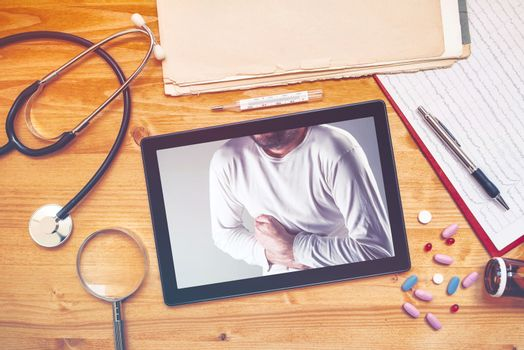 Tablet computer with picture of man having pain in abdomen