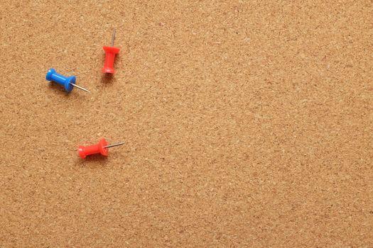 Three push pins on a cork noticeboard
