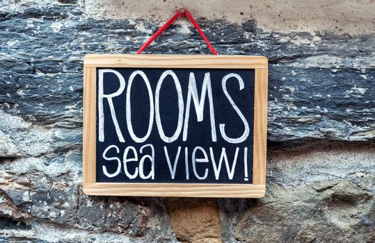 Rooms available chalkboard sign hanging on stone wall at a hotel