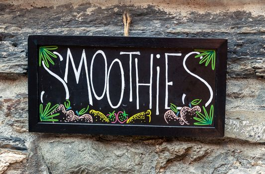 Smoothies available chalkboard sign hanging on stone wall