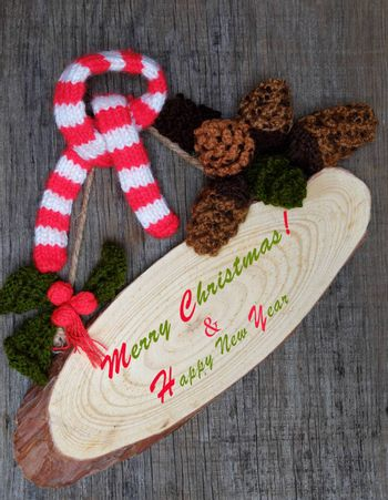 Nice handmade ornament for winter holiday, group of knitted pinecone, holly leaf, berries knit from yarn, message Merry Christmas on tag, nice Xmas background