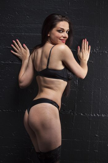 smiling woman in underwear on a black wall
