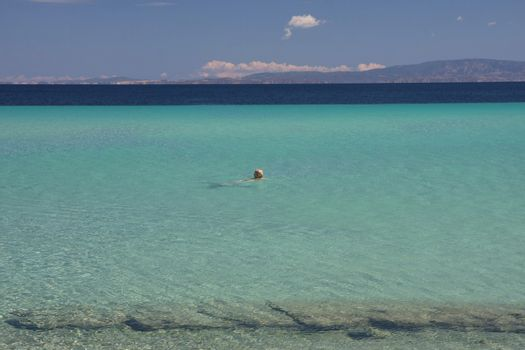 Woman enjoying swimming in sthe sea with fantastic colours